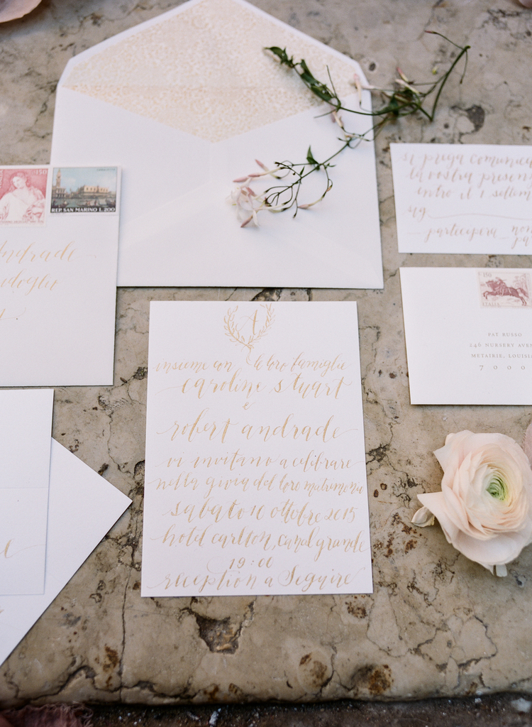 White invitation suite with gold cursive lettering and blush accents