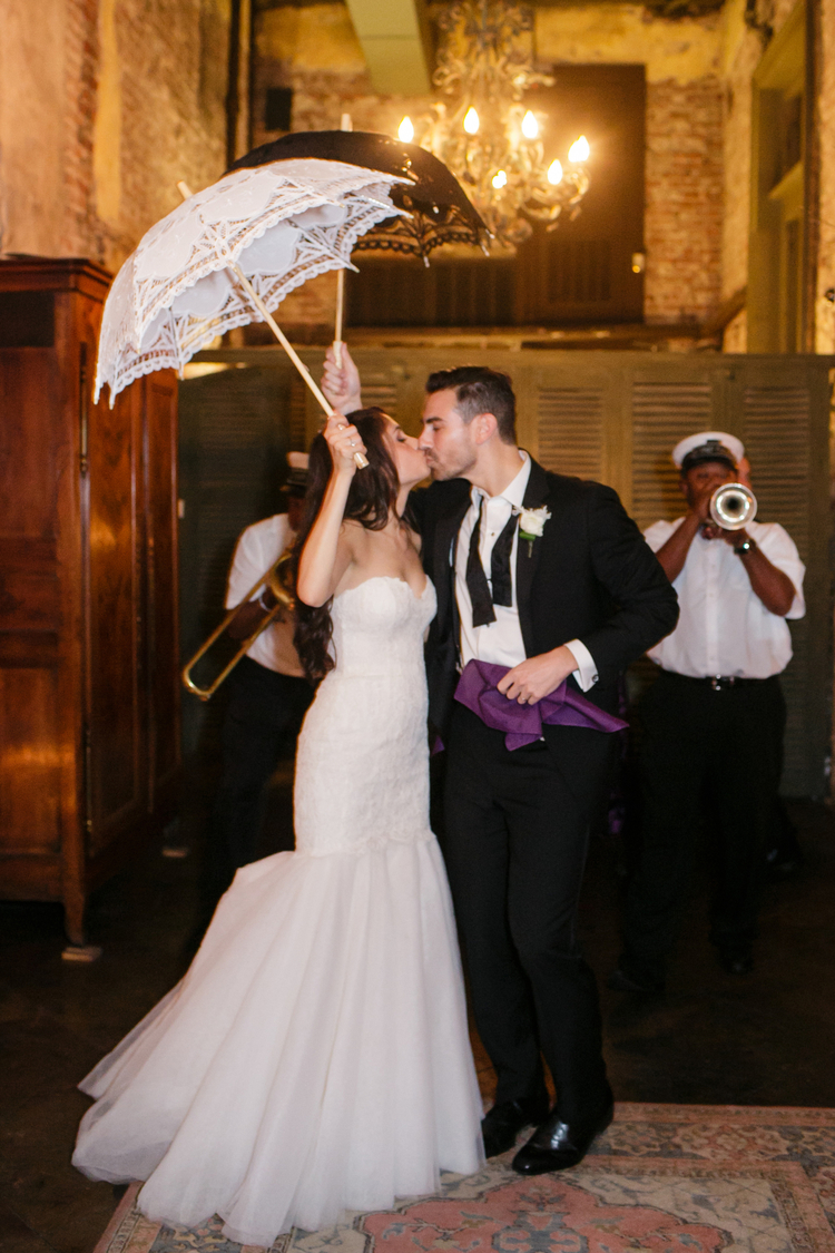 Bride and groom kissing under their second line umbrellas with the jazz band in the back