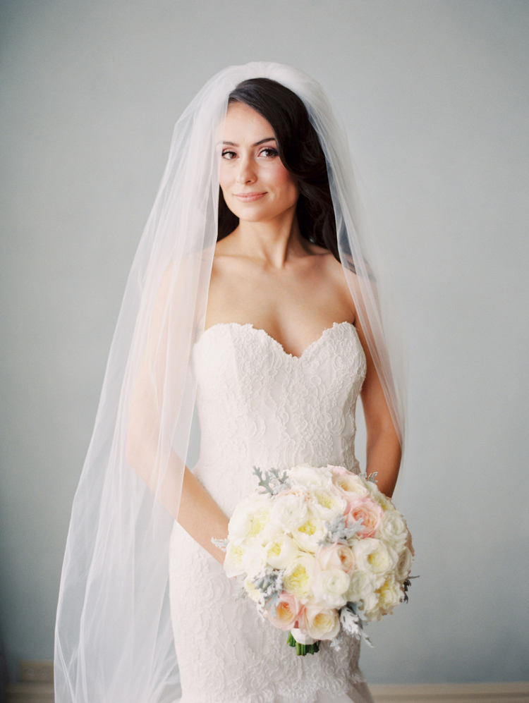 Bride posing in her wedding dress with her long veil over her shoulders holding her white and peach colored floral bouquet