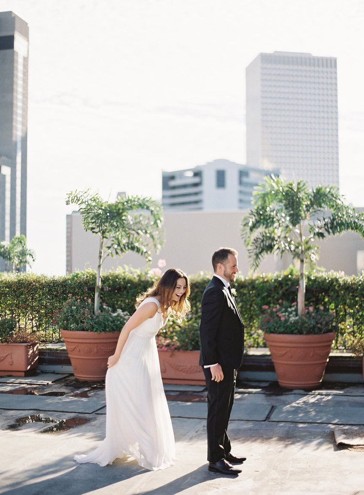 "Bride and Groom on a rooftop in New Orleans doing a ""first look"" and smiling in front of hedges"