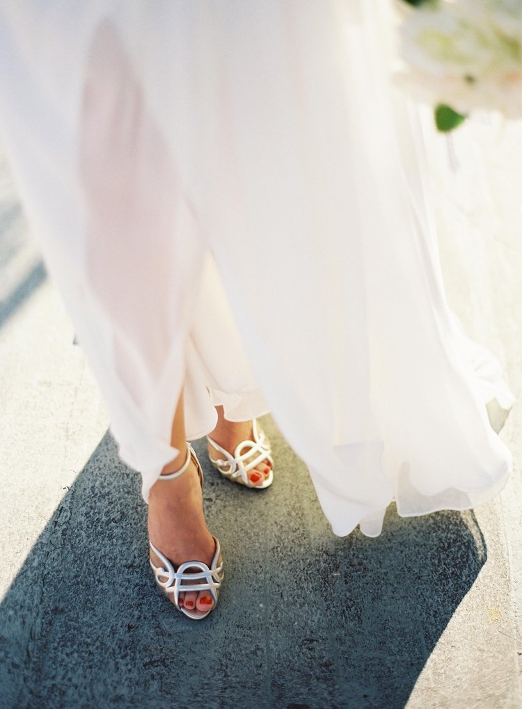 Detail shot of the brides white dress flowing in the wind and her silver open toe shoes