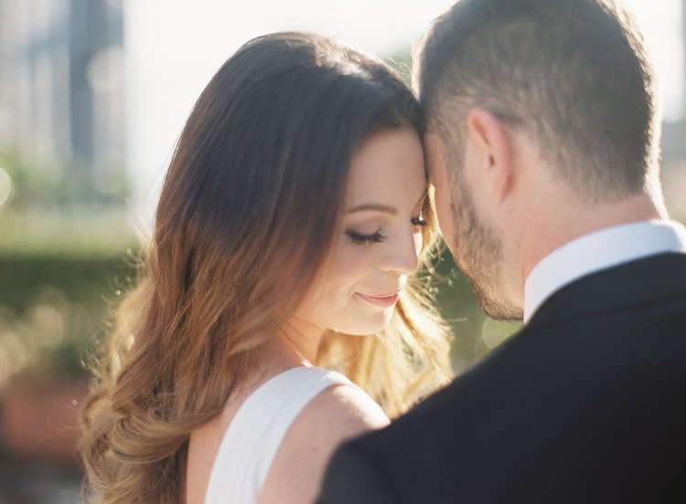 Bride and groom touch foreheads while taking a beautiful photo