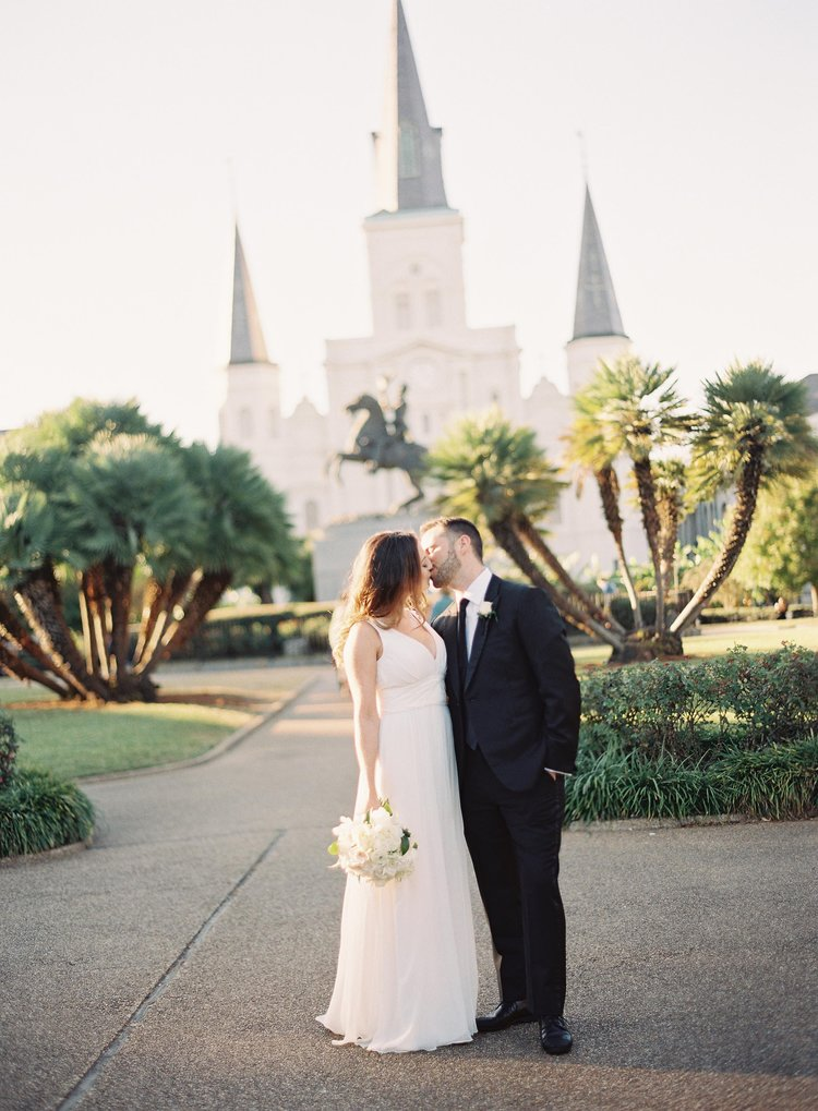 A bride and groom kiss in front of the St. Louis Cathedral in the New Orleans French Quarter