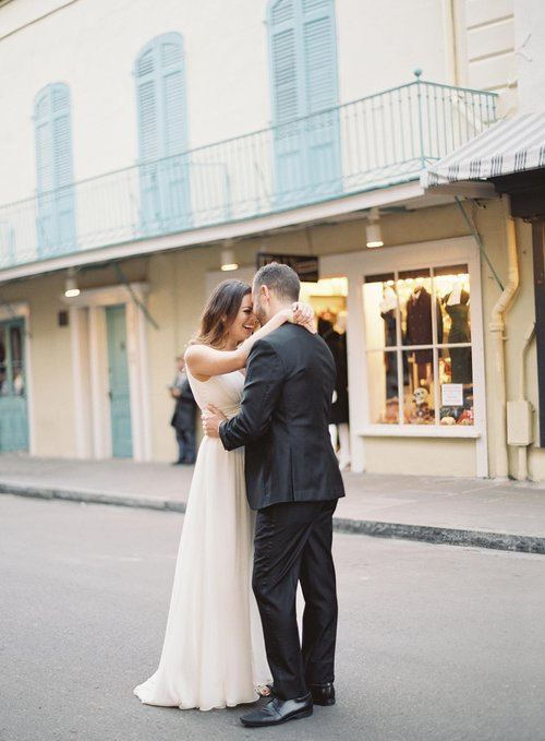 bride hugs her groom in the street in the french quarter