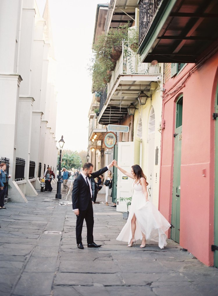 Groom twirls bride while dancing in the French Quarter in New Orleans