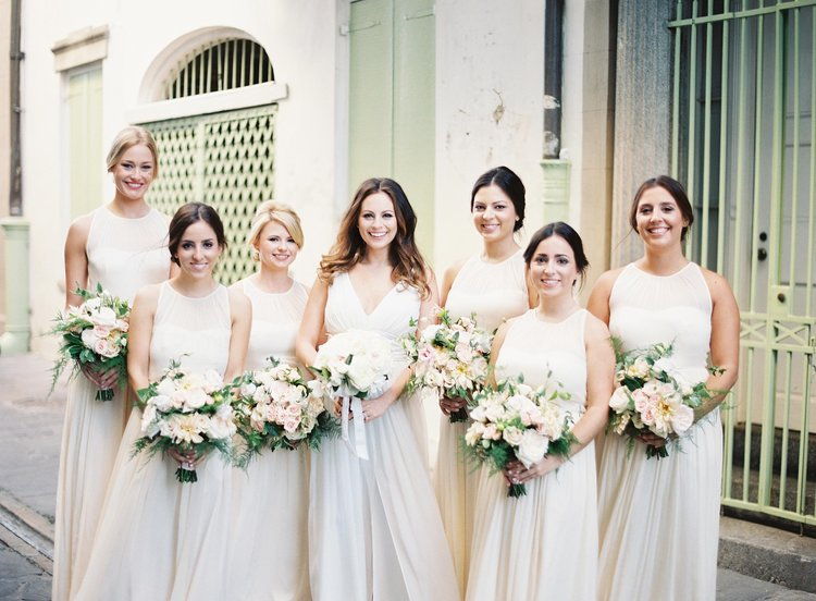 Bride and Bridesmaids with long white dresses and light florals pose in the streets of New Orleans