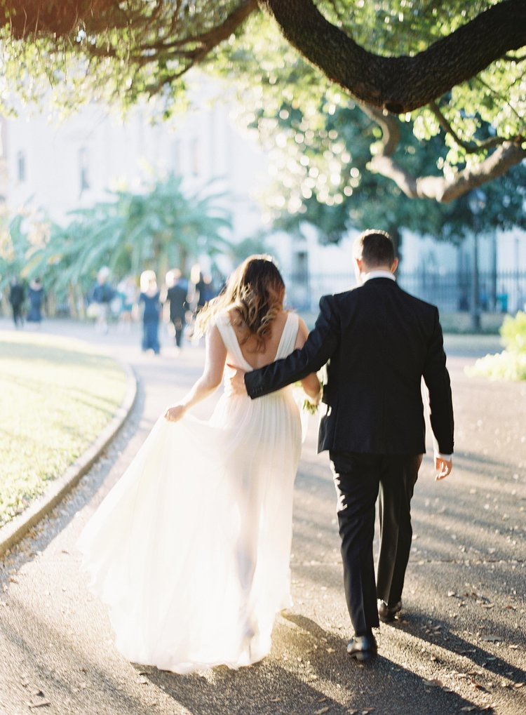 Bride and groom walking in the French Quarter with Grooms hand on brides back