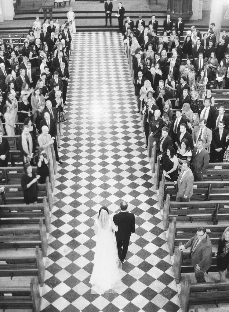 Arial view of a father walking the bride down the isle in a church with black and white checkered tiles and guests standing int the pews