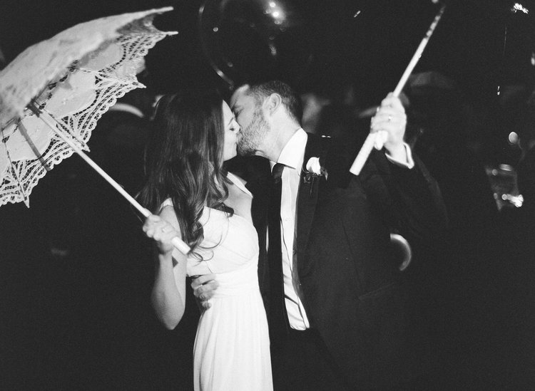Black and white photo of the bride and groom kissing under their second line umbrellas
