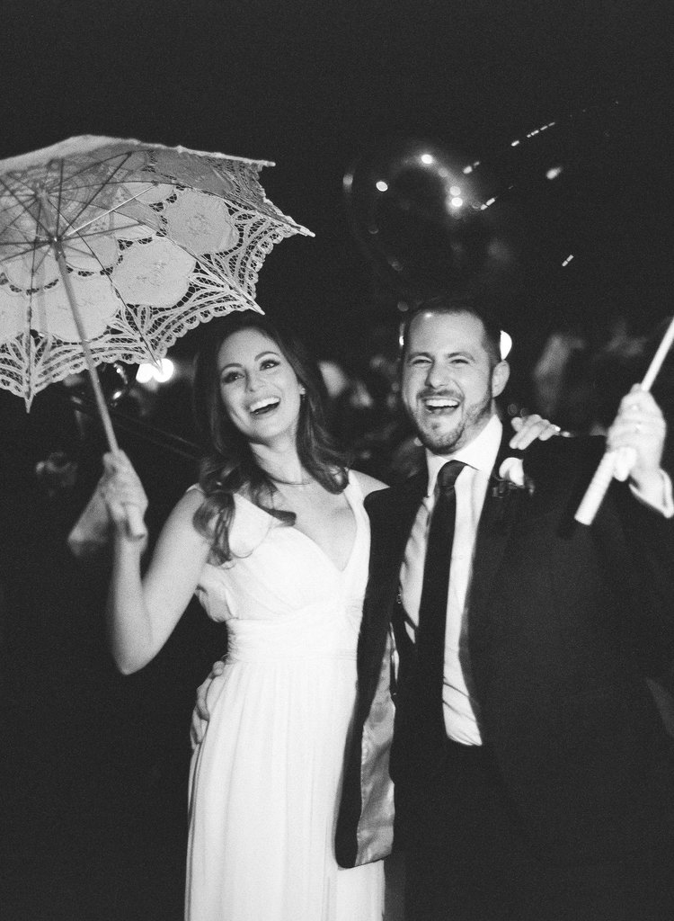 Bride and groom smile and cheer while second lining with their umbrellas and hankies