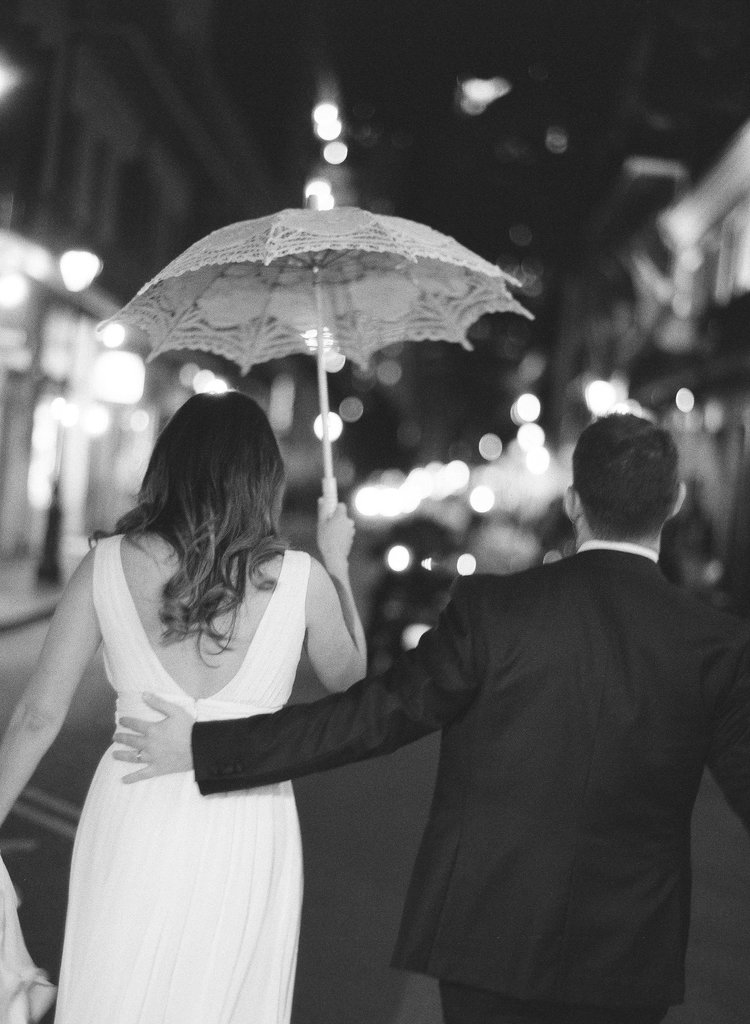 Bride and groom walking down the streets of New Orleans with their second line umbrellas