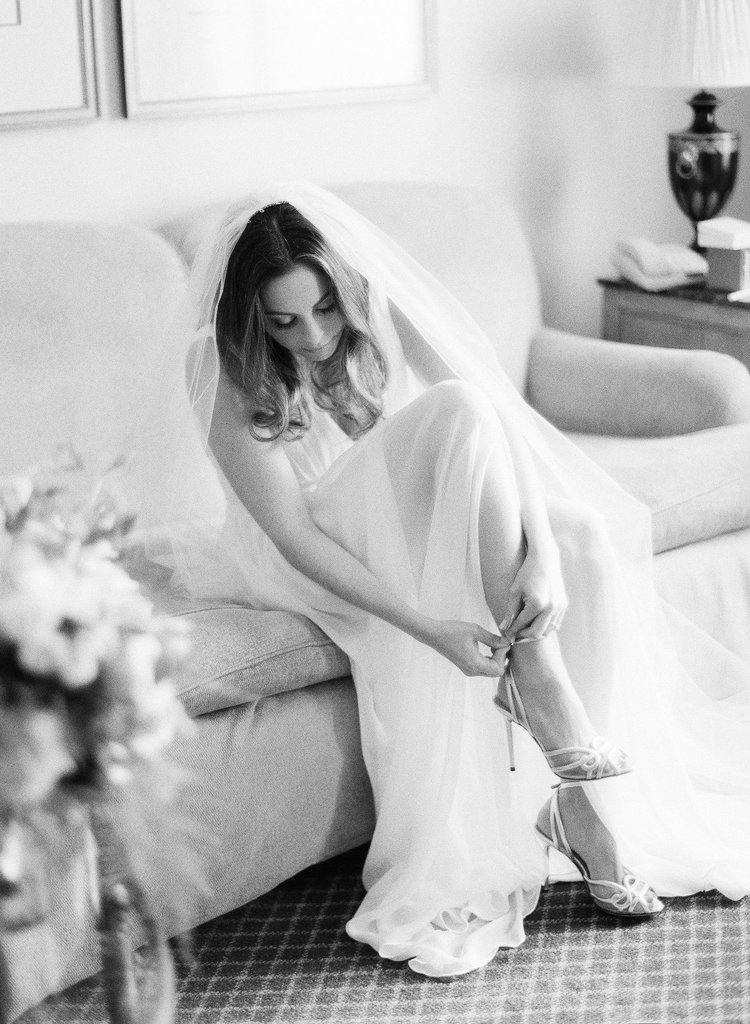 Black and white photo of a bride in her dress and veil putting on her wedding shoes