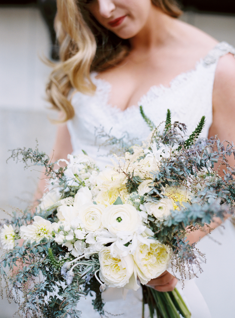 Bride holding her luscious bouquet of white ranunculus, pale yellow buttercups and greenery