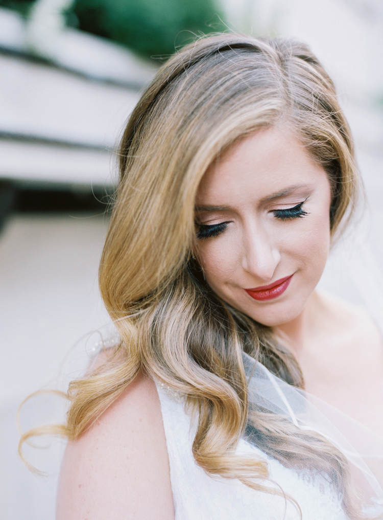 portrait photo of a bride looking over her shoulder with red lipstick on
