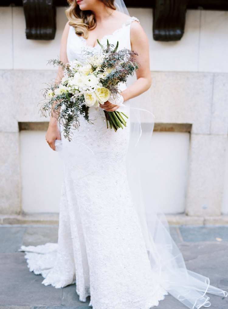 Bride standing in her white wedding gown hold a bouquet of white, light yellow and green florals