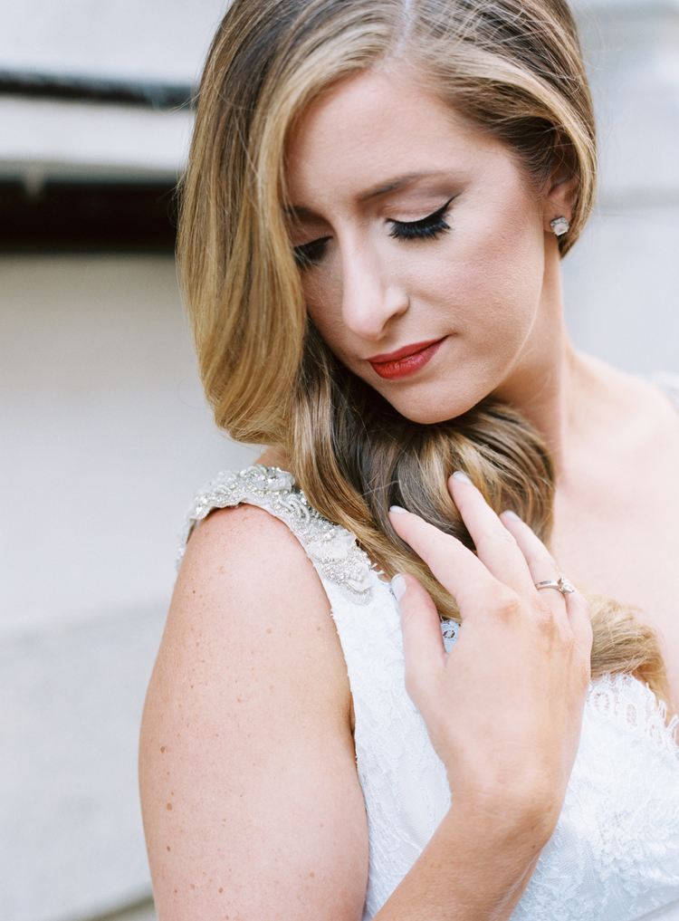 Bride gazing over her shoulder in her beaded wedding gown wearing red lipstick