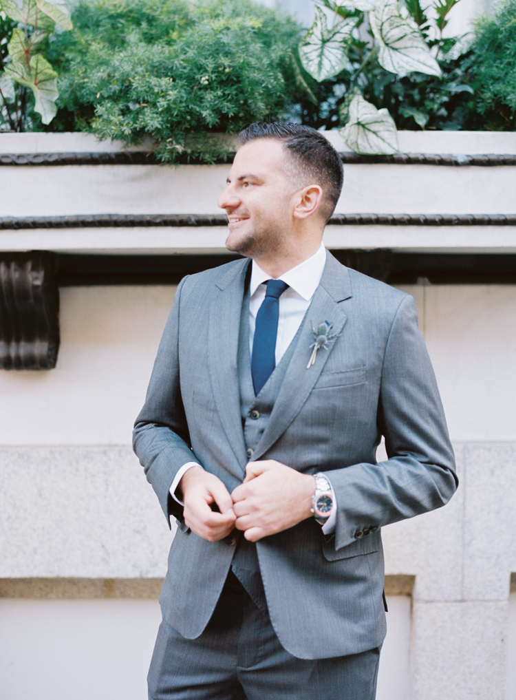 Groom wearing a grey suit and blue tie with a thistle boutonnière