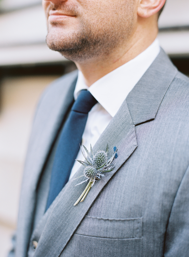 Up close of the grooms thistle boutonniere and blue tie