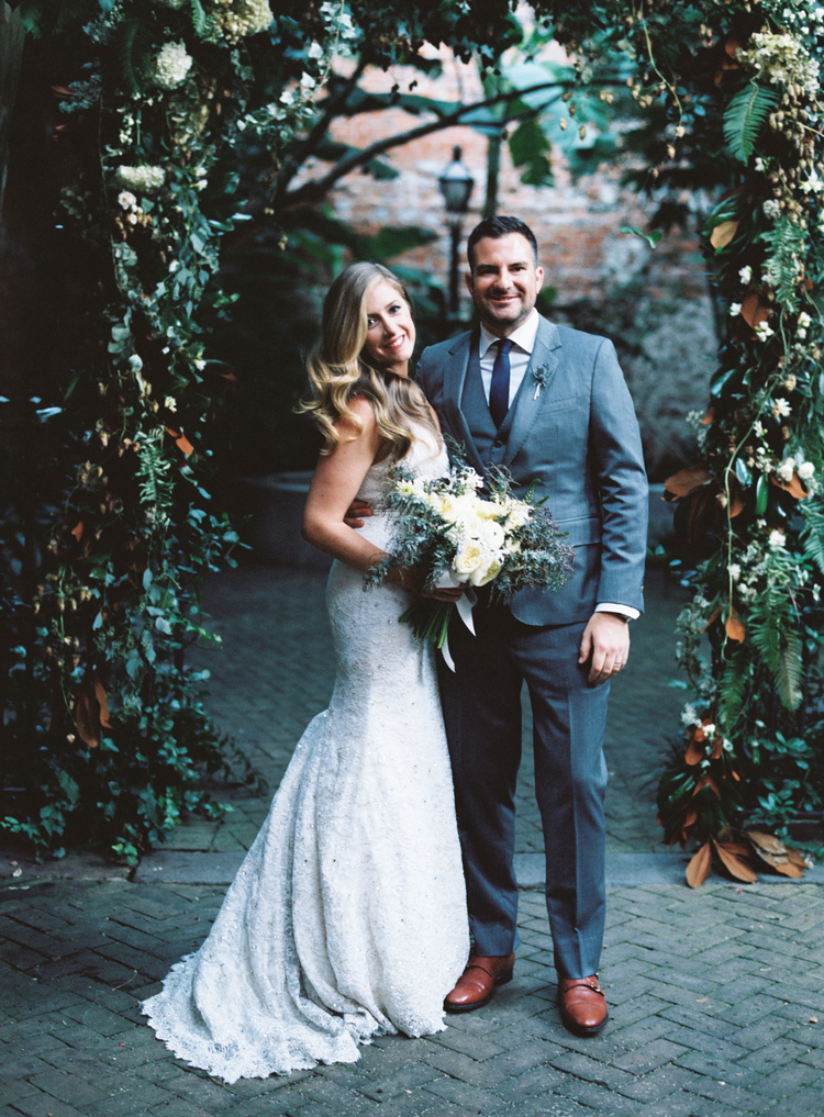 Bride and groom standing under a green arch with white flowers
