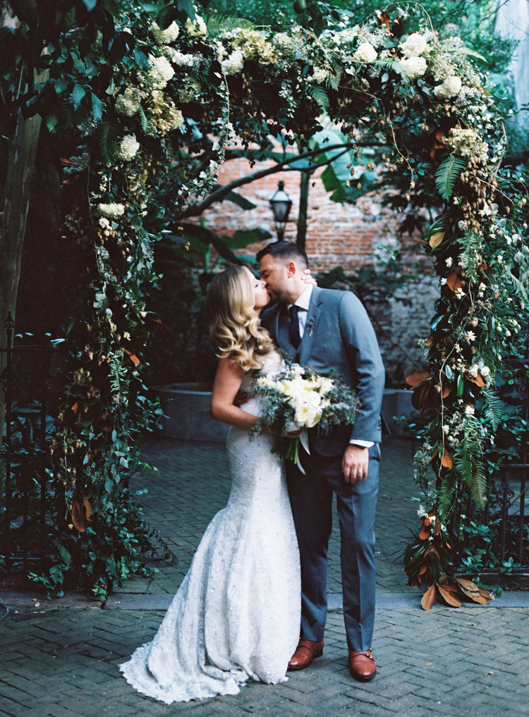 Couple kissing under a white floral and green archway bride holding her lush bouquet