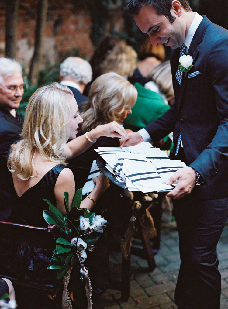 Usher at a wedding wearing a white rose boutonniere passing out white and black programs
