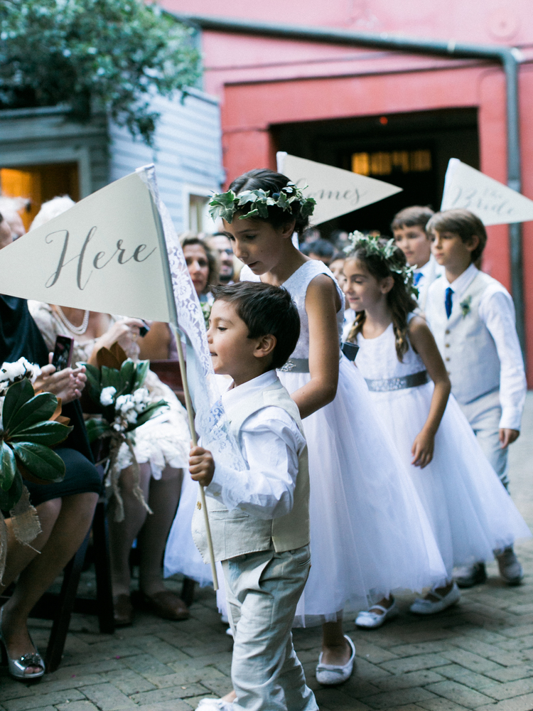 flower girls and ring bearers walk down the aisle with here comes the brides signs wearing white dresses and khaki suits