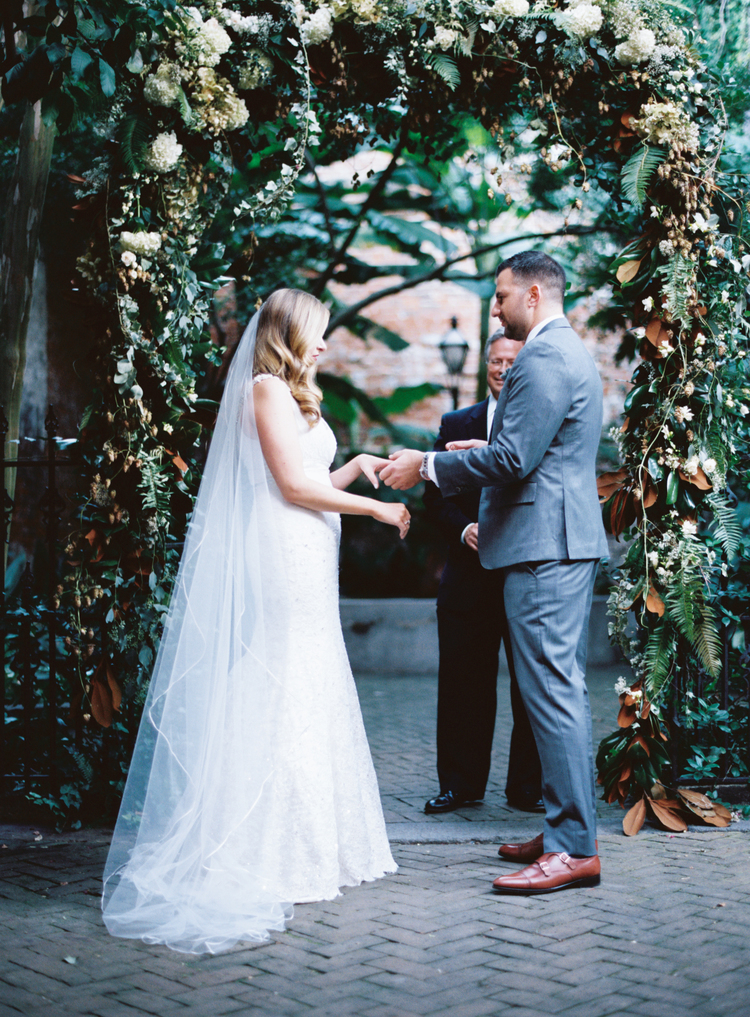 Bride and groom at alter putting wedding bands on under a green arch