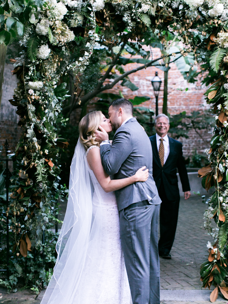 Couple kissing under a lush green and white floral at their wedding