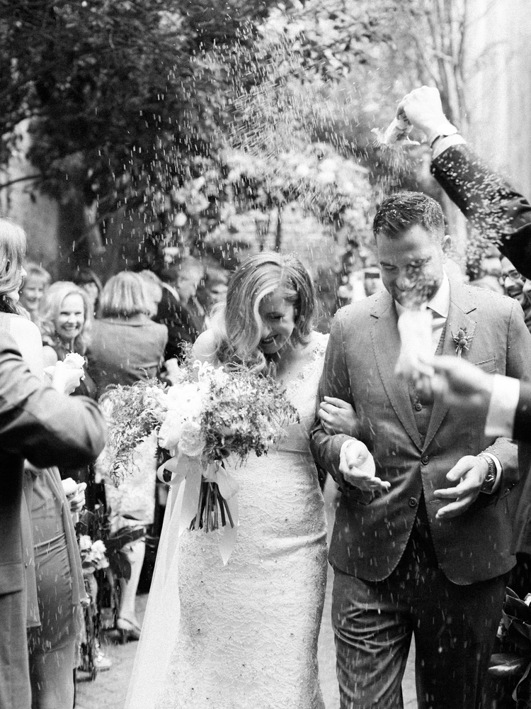 black and white photo of guests throwing rice over the bride and groom as they walk down the aisle married