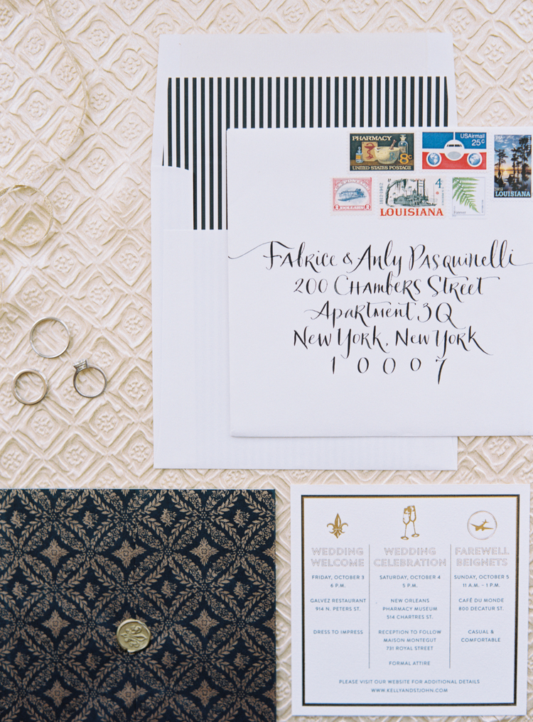 black and white invitations with a colorful stamp story next to the wedding bands