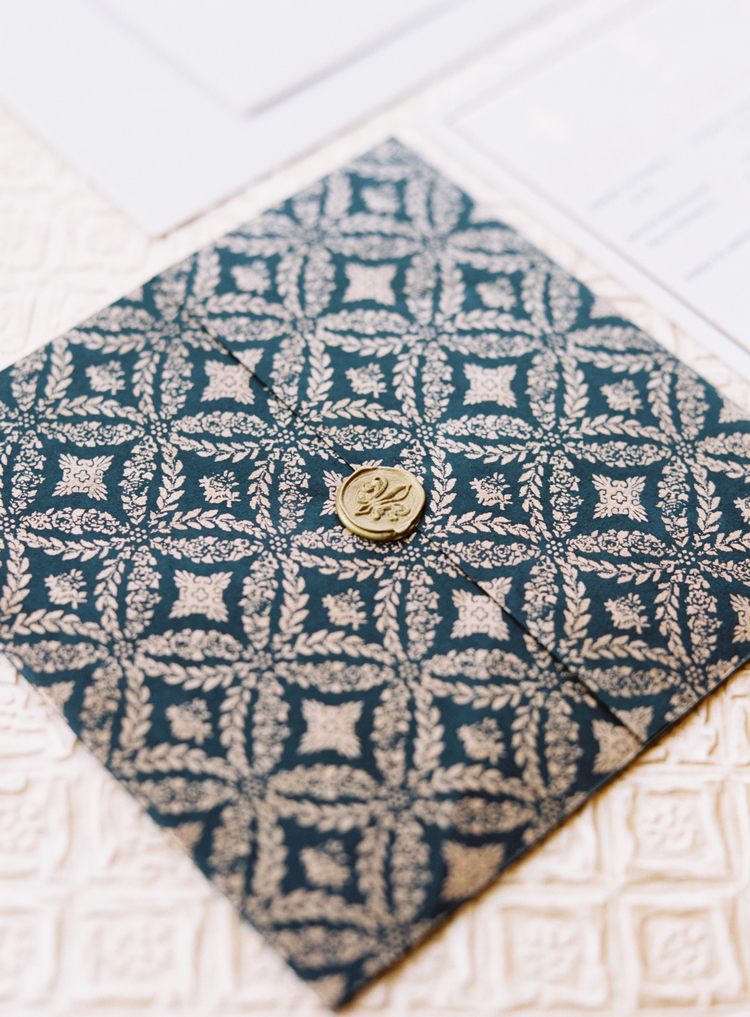 gold letter seal with a fleur de lis on top of gold and navy design of the invitations