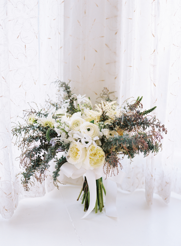 Brides bouquet with white ranunculus, white peonies and greenery with a white sash