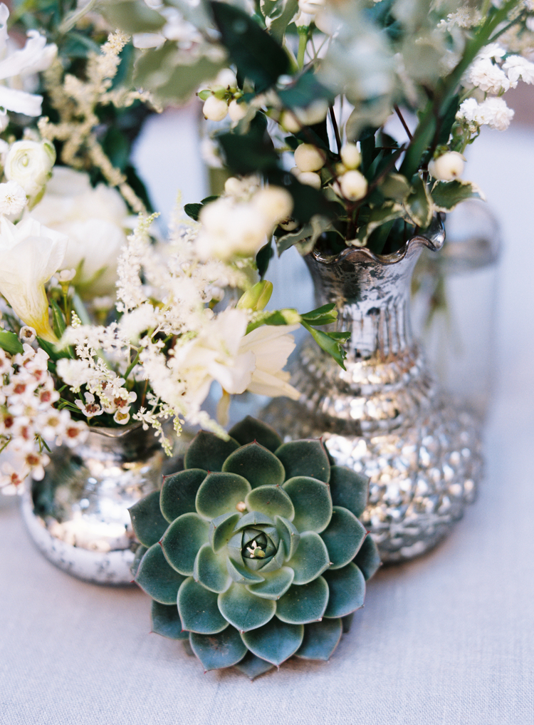 silver vases with white flowers and succulents