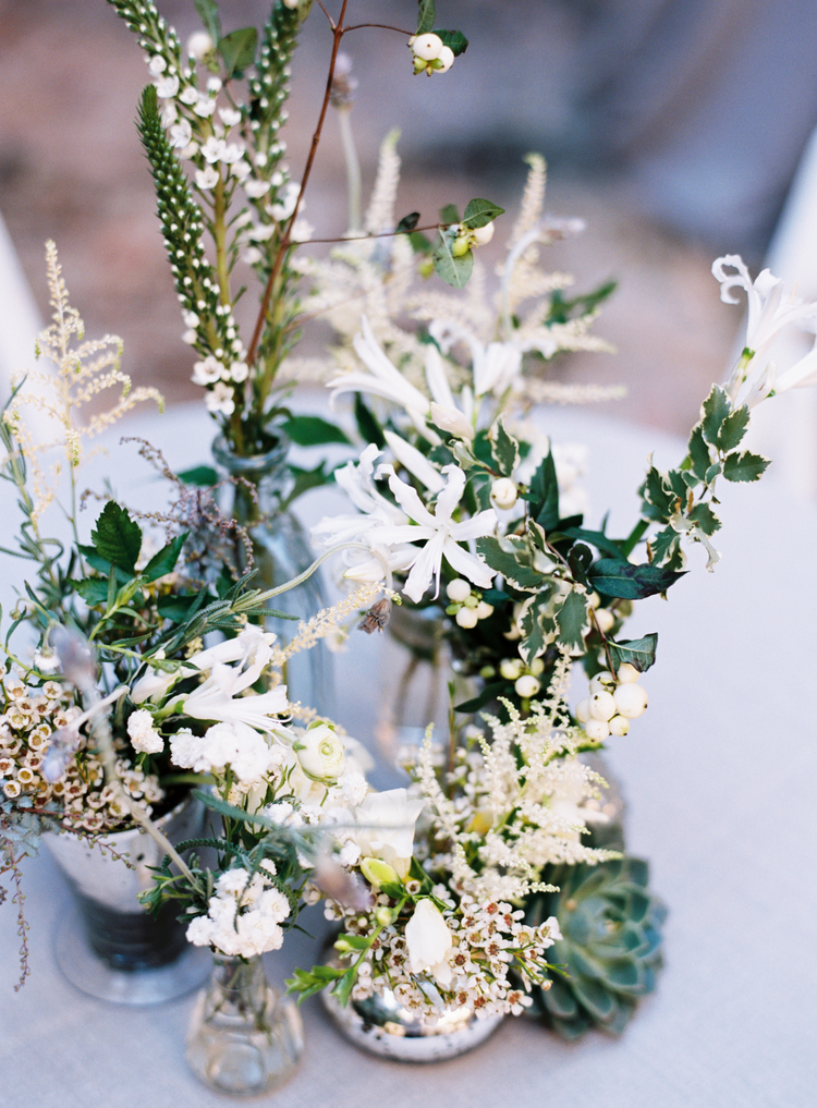 white and green flowers in an arrangement on a table in vases
