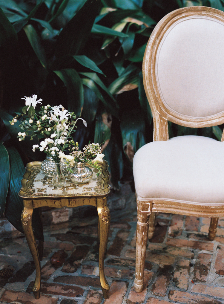 tan upholstered round back chair next to a gold side table with small white delicate flowers in vases