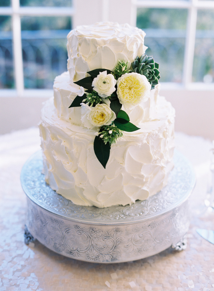 three tiered pallet icing with white flowers and leaves as decor