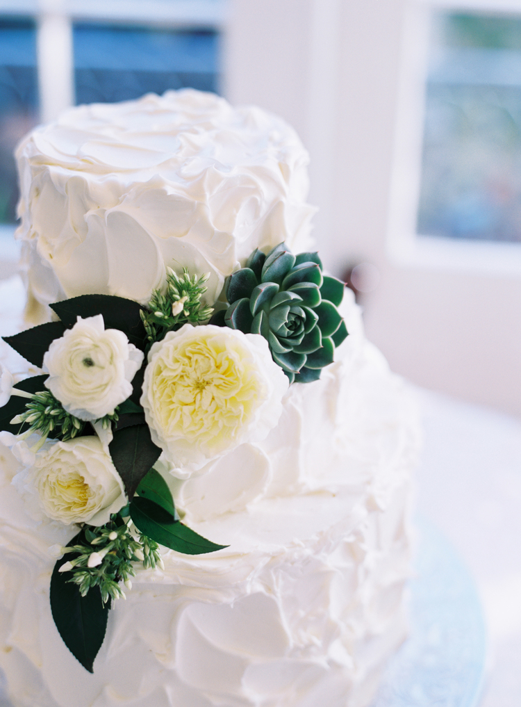 creative white wedding cake with white ranunculus and green succulents on the side