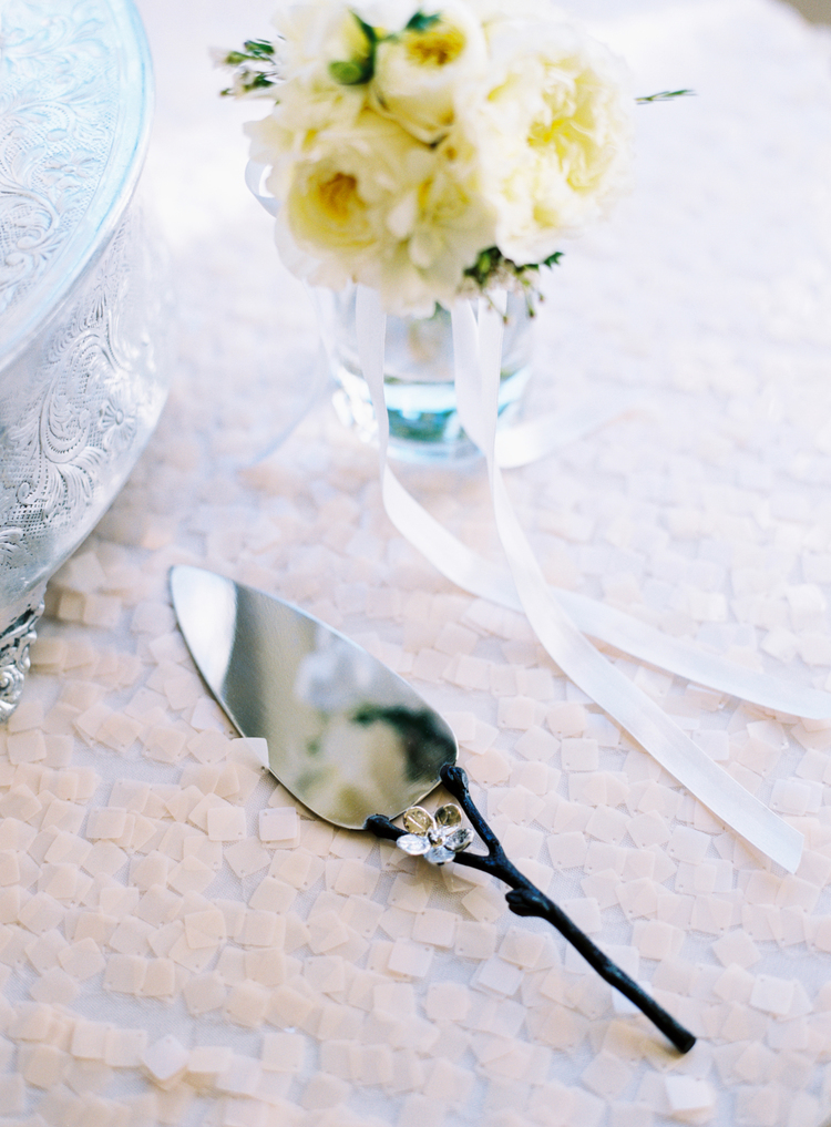 silver wedding cake server next to a silver cake stand and a bouquet of light yellow flowers