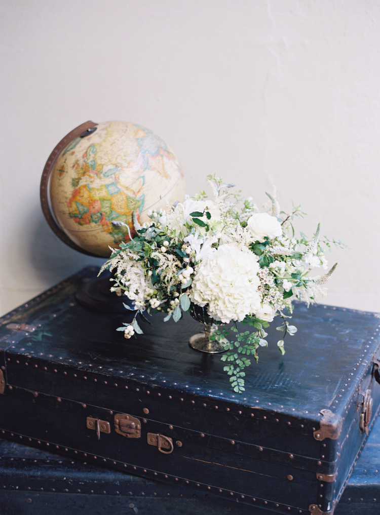 white hydrangeas with greenery next to an antique globe sitting on an antique suitcase
