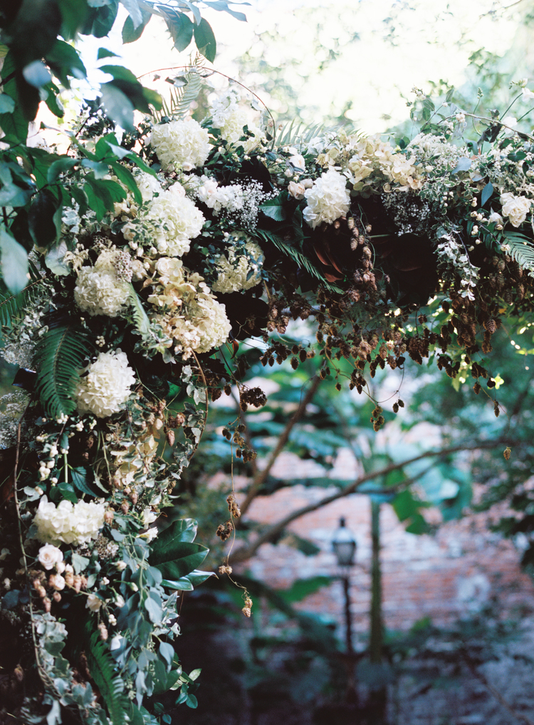 detail photo of white hydrangeas in a green ivy arch