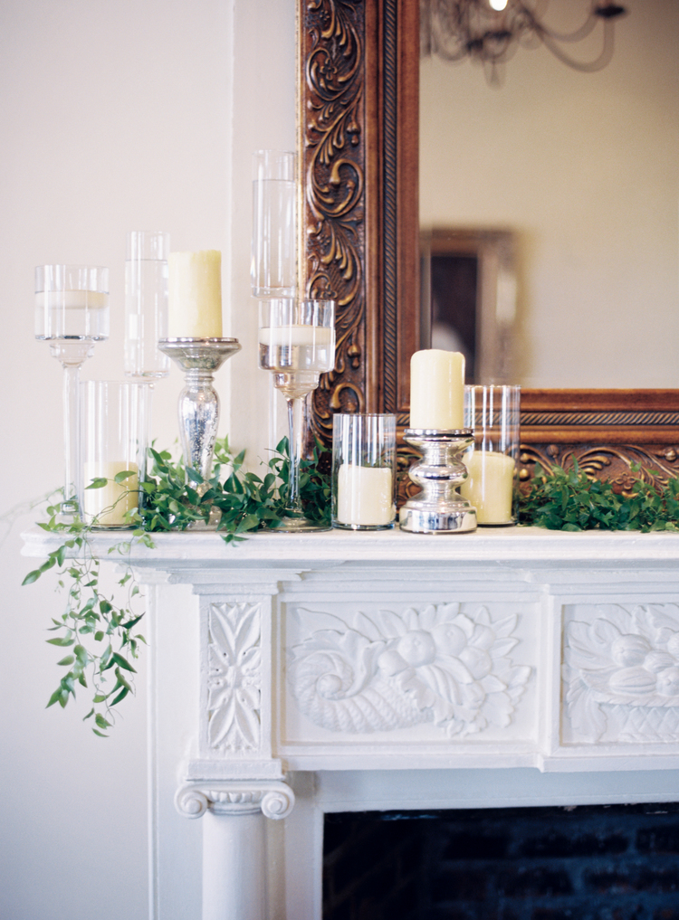 candles and clear candle vases sitting on top of an intricate white fireplace with a gold mirror