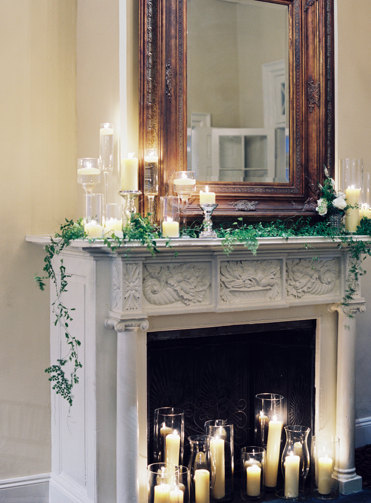 distressed white fireplace with candles and greenery on top and a gold mirror above