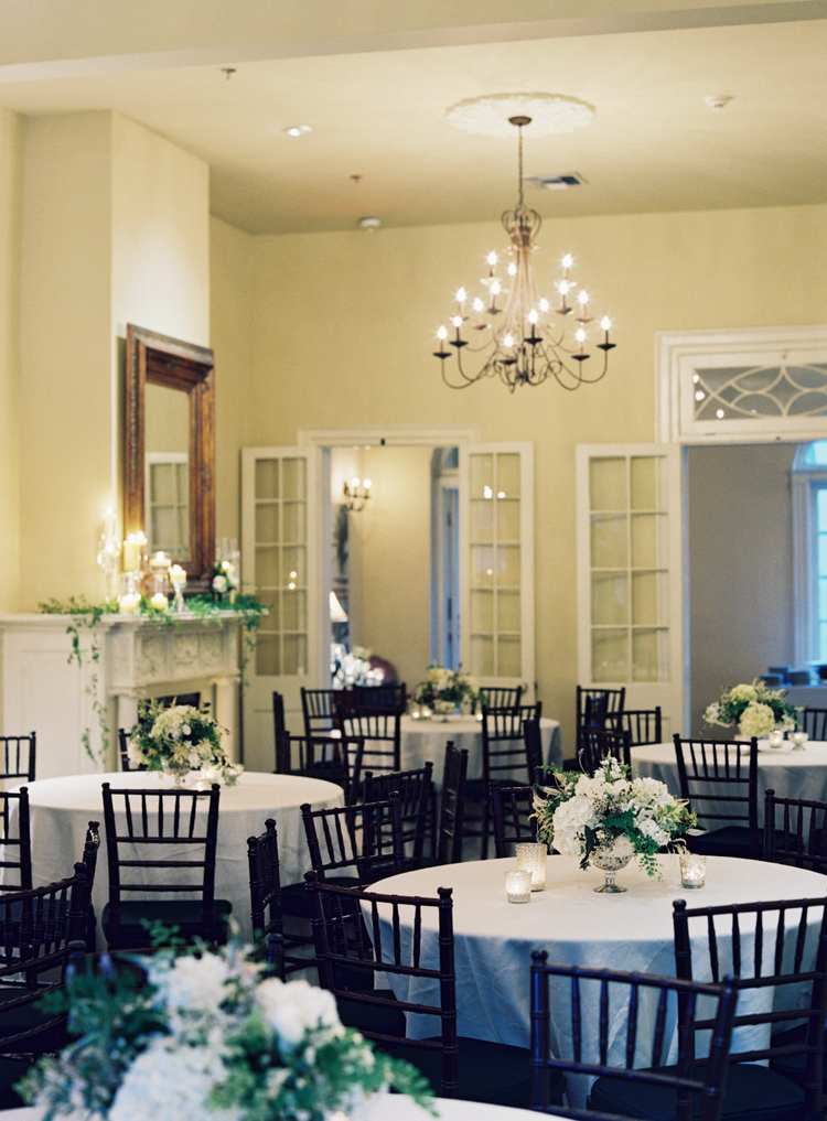 Room with round tables, white linens with white hydrangea centerpieces on top of the tables