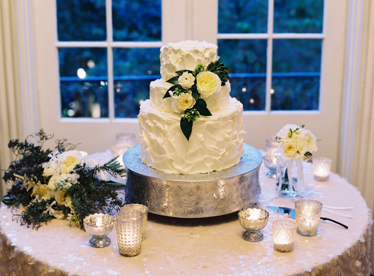 3 tiered white wedding cake on a sparkly sequin table linen with tea lights and candles around the table