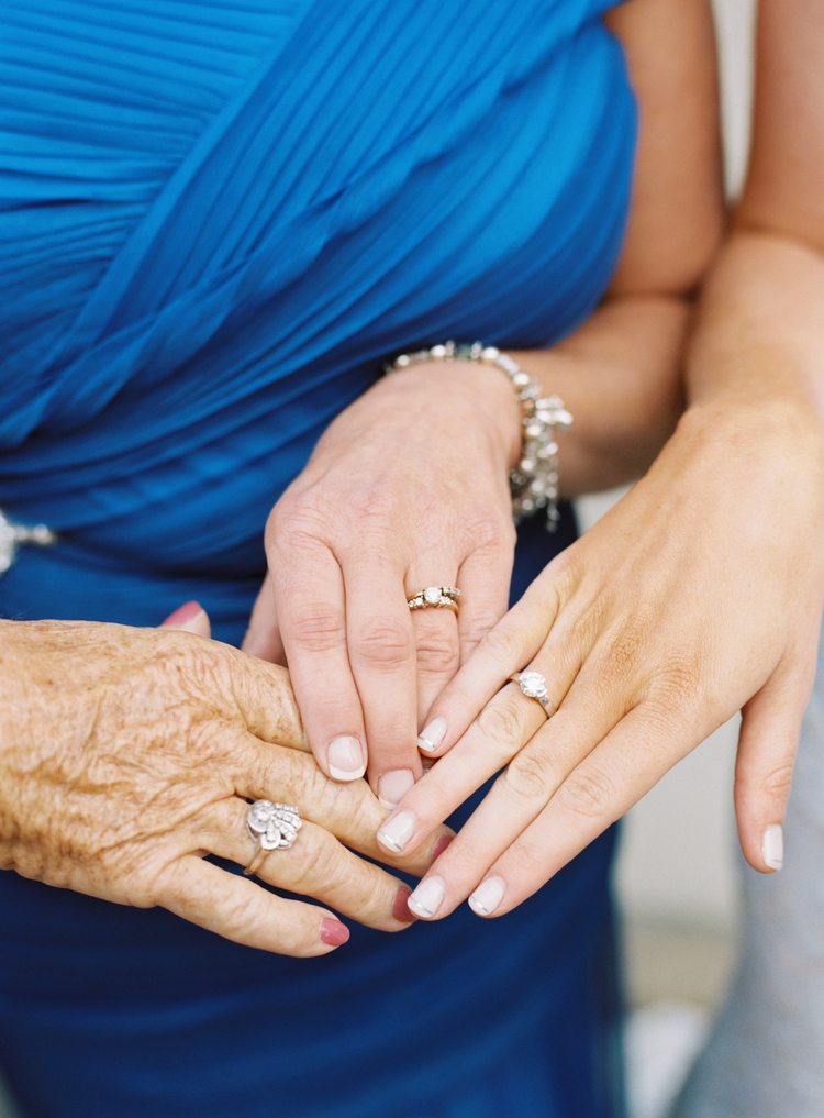 three generations of ladies holding their hands out showing their engagement rings