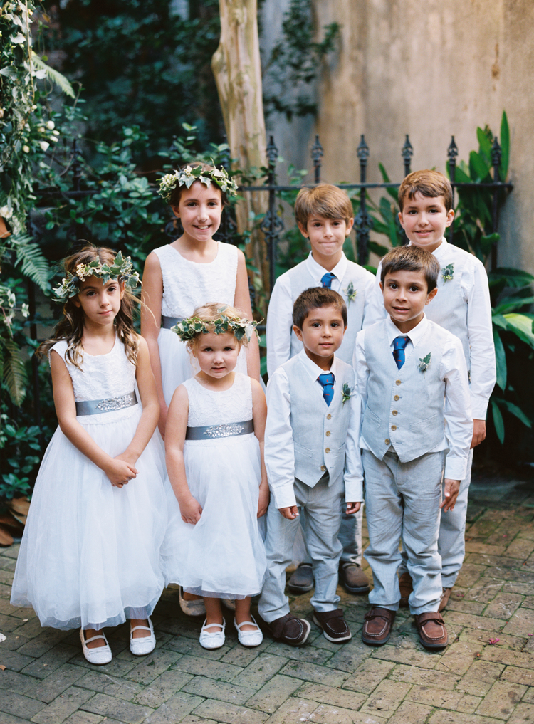 flower girls in white dresses with silver sashes and green leaf headbands, ring bearers in grey tuxes and blue ties