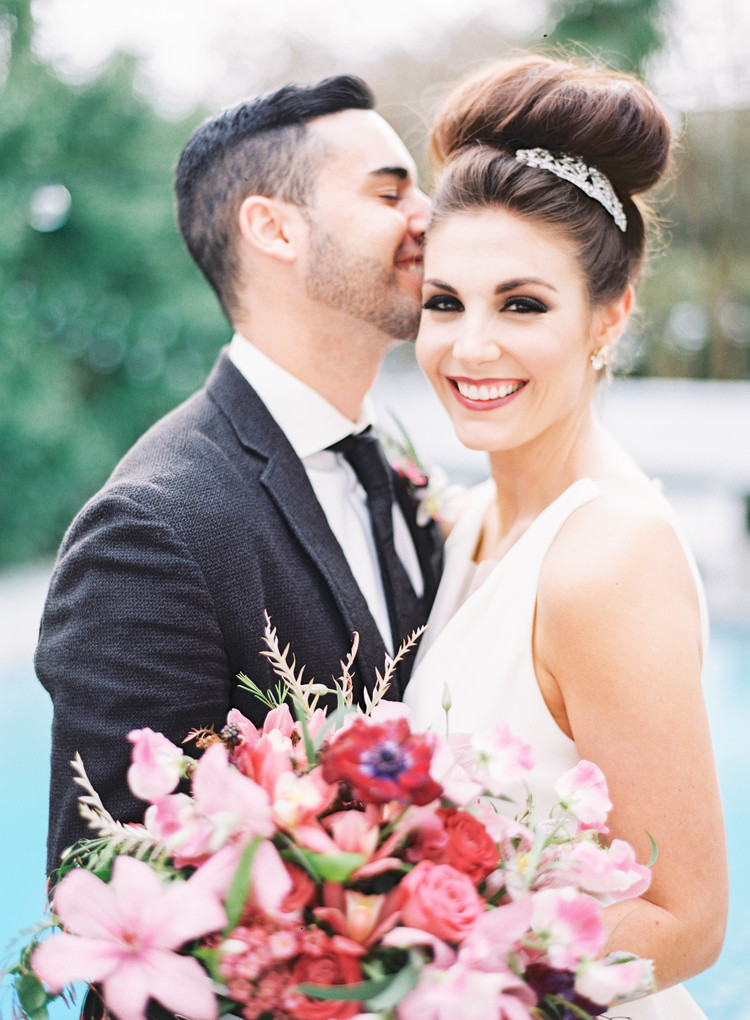 Groom kissing the bride on the cheek while she smiles holding her pink floral bouquet