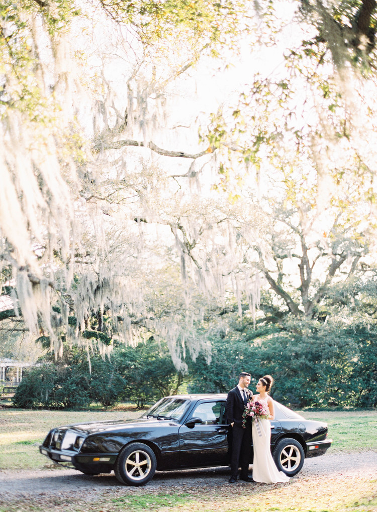 Bride and groom next to their black getaway car outside in front of lush oak trees