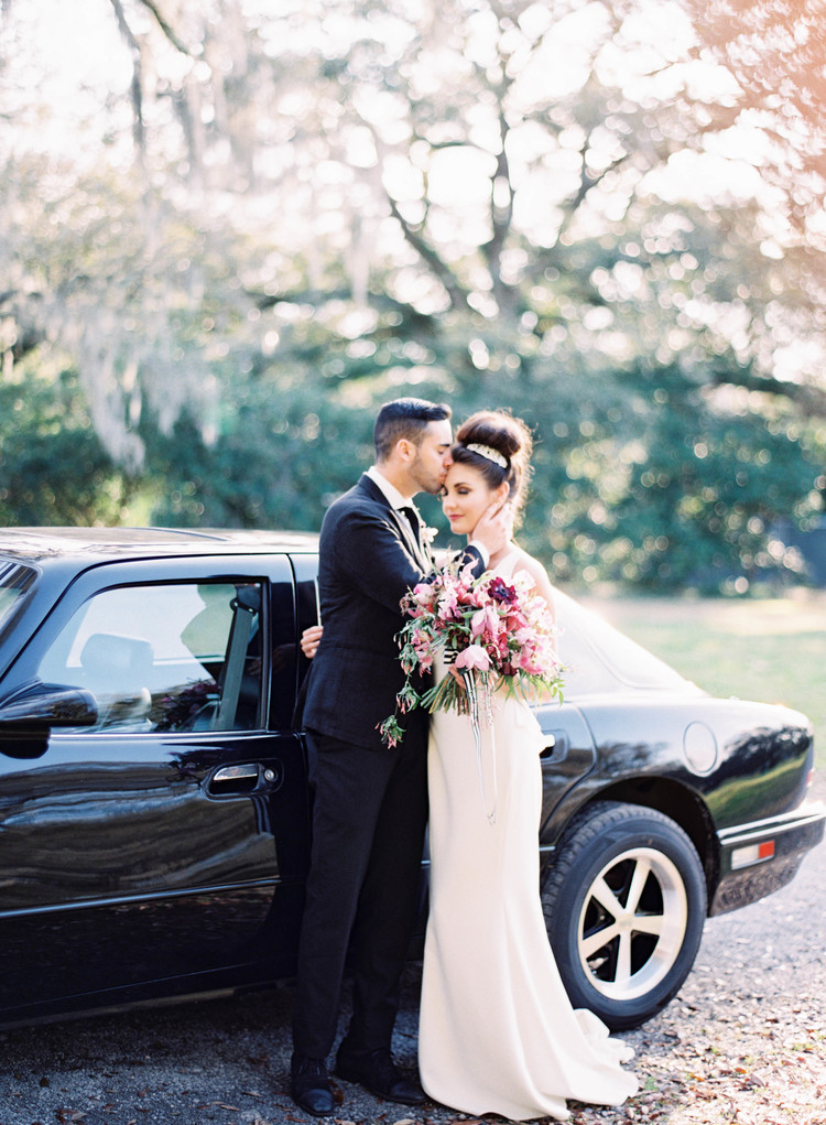 Groom kissed brides forehead in front of a getaway car with oak trees and moss in the background