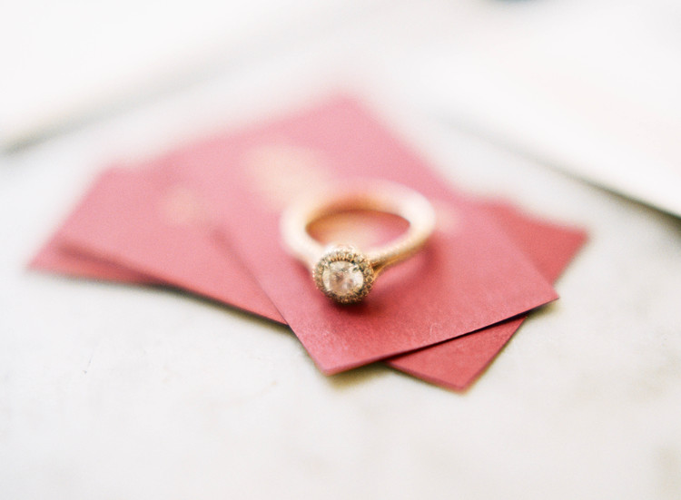 Yellow gold engagement ring sitting on top of red escort cards
